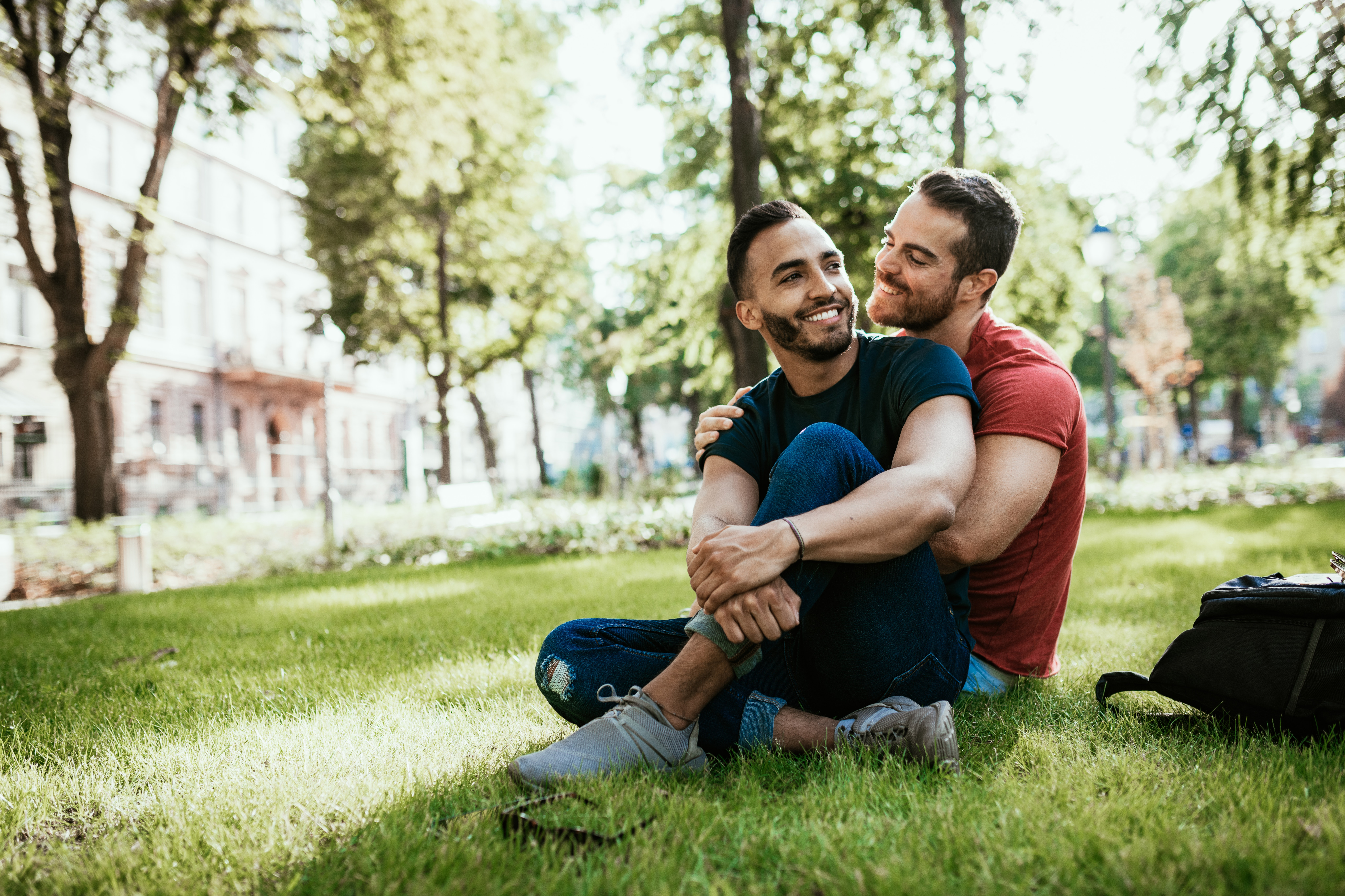 couple embrace while sitting on the grass